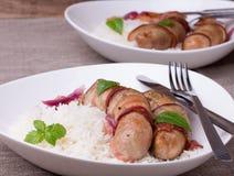 Grillade bavariankorvar med ris och mintkaramellen på den vita maträtten Royaltyfri Bild