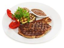 Grillade biffar, bakade potatisar och grönsaker på den vita plattan. Royaltyfria Bilder