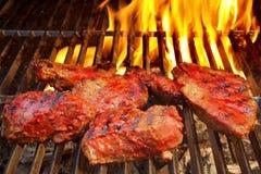 Grillade biffar på BBQ-spisgallret och flammor i bakgrund, XXXL Arkivfoto