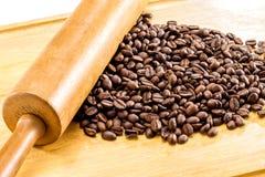 Grillade bruna kaffebönor och träkavel på wood backgr Royaltyfria Foton