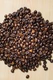 Grillade bruna kaffebönor på trätabellen Royaltyfri Bild