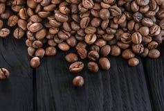 Grillade doftande bönor av svart kaffe sprids på en svart tabell arkivfoto