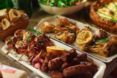 Grillade fega kött och korvar, paj och sallad för matställe arkivbilder