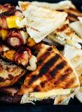 Grillade fega köttsteknålar rullande med bacon grilla steknålar med grönsaker och grillat pizzabröd Arkivfoton
