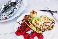 Grillade grönsaker bredvid en grillad forell i matlagning omkullkastar Royaltyfri Foto