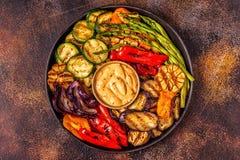 Grillade grönsaker på en platta med sås arkivfoto