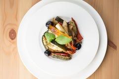 Grillade grönsaker på en vit platta på träbakgrund överkant VI arkivbilder