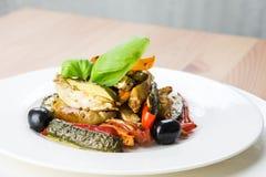 Grillade grönsaker på en vit platta på träbakgrund royaltyfri fotografi