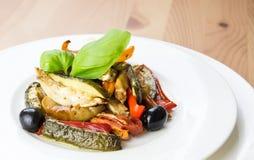 Grillade grönsaker på en vit platta på träbakgrund arkivfoton