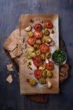 Grillade grönsaker: tomater och brussels groddar, vitlök, chilipeppar och smällare på lantlig skärbräda Arkivbild