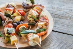 Grillade grönsaksteknålar på plattan Arkivfoto