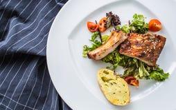 Grillade grillfestgrisköttstöd i en vit platta som meny i bar fotografering för bildbyråer
