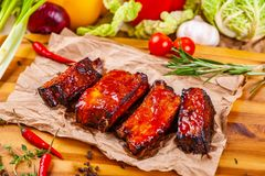 Grillade grillfestgrisköttstöd med kryddor och örter på träbräde fotografering för bildbyråer