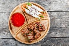 Grillade griskött och grönsaker med ny sallad och bbq-sås på skärbräda på träbakgrundsslut upp besegrar varm meat Royaltyfria Bilder