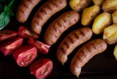Grillade grisköttkorvar, grillade potatisar och nya tomater Top beskådar close upp royaltyfri foto