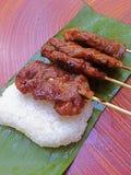 Grillade grisköttpinne och klibbiga ris med den gröna behållaren, bananblad Royaltyfria Bilder