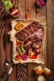 Grillade grisköttstöd tjänade som med grillad havre, salat, bbq-sås, saltar peppar och gurkan på pergamentpapper på ett trä Fotografering för Bildbyråer