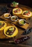 Grillade höna och Foie Gras taco tjänade som på träskärbräda med olika såser, och mexikanen torkade chili royaltyfria bilder