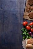 Grillade jordkotletter för biff för nötköttkötthamburgare med smaktillsats, tomater, persilja och bullen på trätabellen, utrymme  Royaltyfria Bilder