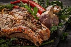 Grillade kött och grönsaker på en svart lantlig bakgrund royaltyfri foto