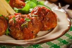 Grillade köttbullar i tomatsås med fransmansmåfiskar och sallad Arkivfoton
