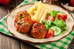 Grillade köttbullar i tomatsås med fransmansmåfiskar och sallad Arkivbild