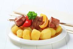 Grillade köttsteknål och potatisar arkivbild