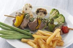 Grillade köttsteknålar och grönsaker med pommes fritespotatisar Fotografering för Bildbyråer