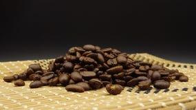 Grillade kaffebönor över trä på svart bakgrund arkivbilder