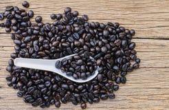 Grillade kaffebönor i den vita skeden Fotografering för Bildbyråer
