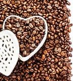 Grillade kaffebönor i en formad vit hjärta boxas på valentin D Arkivfoto