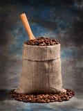 Grillade kaffebönor i en påse med en skopa Arkivfoton