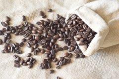 Grillade kaffebönor i en säckvävpåse Arkivfoto