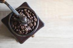 Grillade kaffebönor i träkaffekvarn Top beskådar Kopieringssp arkivfoto