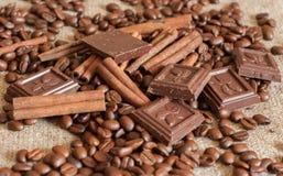 Grillade kaffebönor, kanelbruna pinnar och stycken av choklad på en säckväv Arkivbild