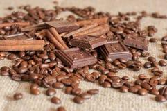 Grillade kaffebönor, kanelbruna pinnar och stycken av choklad på en säckväv Fotografering för Bildbyråer