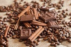 Grillade kaffebönor, kanelbruna pinnar och stycken av choklad på en säckväv Royaltyfri Bild