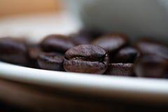 Grillade kaffebönor med den vita koppen på den vita wood tabellen Kaffe Arkivbild