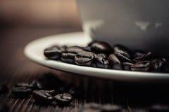 Grillade kaffebönor med den vita koppen på den vita wood tabellen Kaffe Royaltyfria Bilder