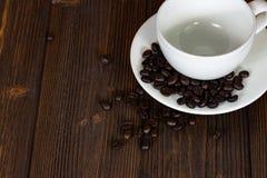 Grillade kaffebönor med den vita koppen på den vita wood tabellen Kaffe Royaltyfri Fotografi
