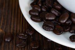 Grillade kaffebönor med den vita koppen på den vita wood tabellen Kaffe Fotografering för Bildbyråer