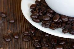 Grillade kaffebönor med den vita koppen på den vita wood tabellen Kaffe royaltyfri bild