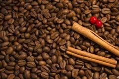 Grillade kaffebönor och kanelbrun bakgrund Arkivbild