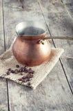 Grillade kaffebönor och kopparkaffekruka Royaltyfria Bilder