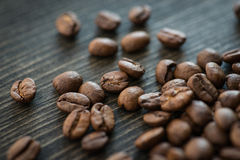Grillade kaffebönor på den gamla trätabellen Royaltyfria Bilder