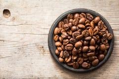 Grillade kaffebönor på den svarta plattan på träbakgrund Royaltyfri Foto