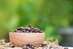 Grillade kaffebönor på den träbunken och säcken/Closeupkaffebönor på naturgräsplanbakgrund arkivfoto