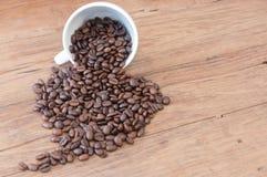 Grillade kaffebönor på den wood tabellen Royaltyfria Bilder