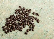 Grillade kaffebönor på en blå konkret tegelplatta Fotografering för Bildbyråer