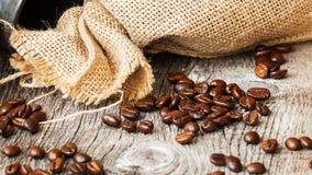 Grillade kaffebönor på en brun träbakgrund med grov ungefärligt vävd säckväv, grungetextur Ställe för din text Arkivbilder